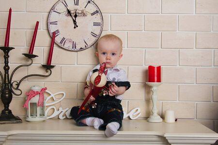 mantel: Foto bambino ragazzo seduto sulla mensola con piano rosso in mano Archivio Fotografico
