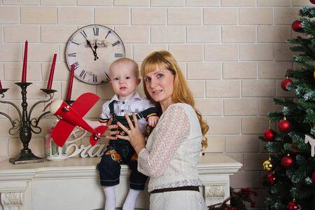 mantel: Foto bambino ragazzo seduto sulla mensola con piano rosso in mano e la madre Archivio Fotografico