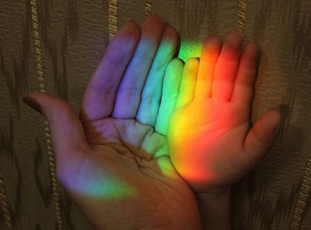 picture of the hand of a child and mother with a rainbow on the background of wallpaper