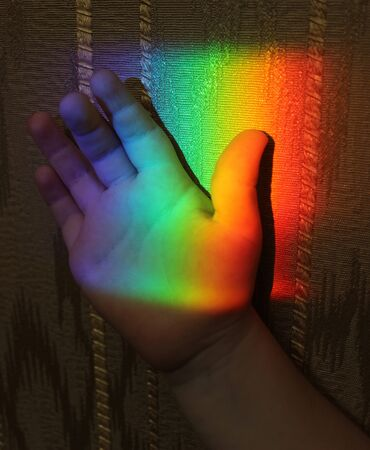 picture of a child hand with a rainbow on a background of wallpaper 스톡 콘텐츠