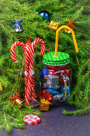 Christmas and New Year decorations and candy canes in cocktail glass jars on a Christmas tree background. The concept of celebrating and decorating Christmas and New Year