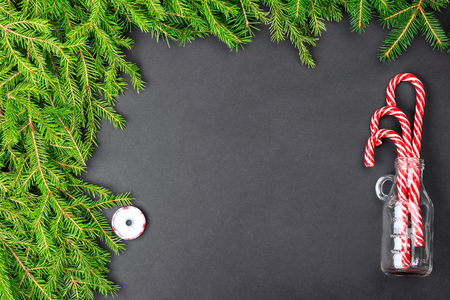 Top view of fir branches, candy canes in a glass cocktail jar frame on a dark background. Christmas, New Year background. Copy Space