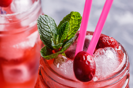 Berry Morse, cocktail of currant and cowberry with ice and fresh mint leaves, with powdered sugar in cocktail drinking jars with colored drinking straws on a concrete table close-up