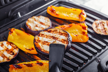 Vegetables: aubergines and yellow pepper on an electric grill. Close-up. Healthy Eating