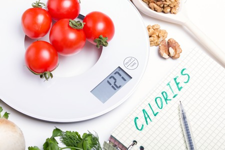 Weighing products, vegetables, fruits on kitchen electronic scales and writing values to the list for calorie counting and making up a proper diet menu, dieting