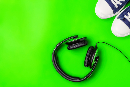 A pair of new stylish sneakers and headphones on a green bright background. Top view. Concept walks to music. Copy space