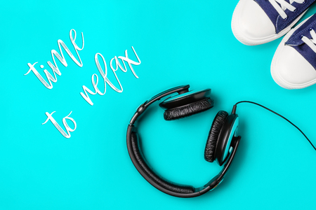 A pair of new stylish sneakers and headphones on a bright blue background and an inscription of time to relax. Top view. Concept walks to music as a way to relax