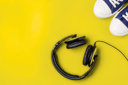 A pair of new stylish sneakers and headphones on a yellow bright background. Top view. Concept walks to music. Copy space