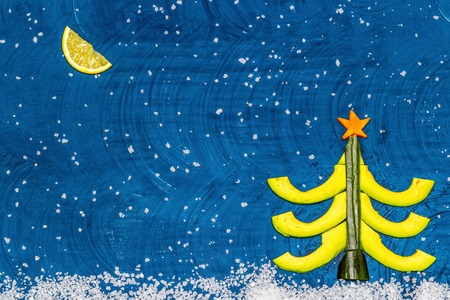 Bright flat food concept of celebrating Christmas and New Year. Christmas tree made from avocado, cucumber and carrots, moon made from lemon wedge, snow from sea salt. Top view Copy space