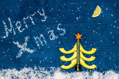 Bright flat food concept of celebrating Christmas and New Year. Christmas tree made from avocado, cucumber and carrots, moon made from lemon wedge, snow from sea salt. Top view