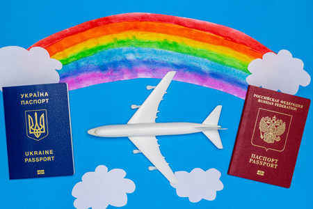 Ukrainian and Russian passports, model airplane, rainbow and clouds of paper on a blue background. The concept of the resumption of air traffic between countries.