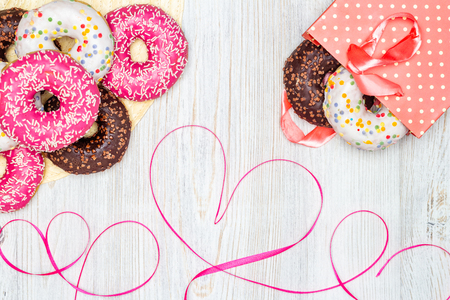 Donuts, gift bag with donuts inside and red ribbon heart on wooden table. Flat lay. Valentines Day celebration concept