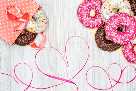 Donuts, gift bag with donuts inside and a red ribbon heart on a wooden table. Flat lay. Valentines Day celebration concept. Stock Photo