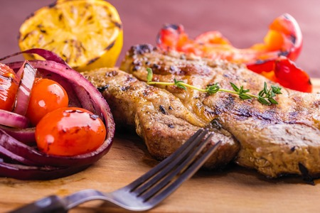 Juicy pork steak with a sprig of fresh thyme, lemon and grilled vegetables close-up.