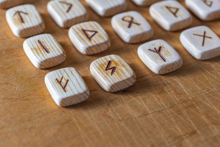 Anglo-saxon wooden handmade runes on the vintage table On each rune symbol for fortune telling is designated.