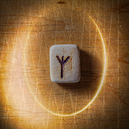 Algiz. Handmade scandinavian wooden runes on a wooden vintage background in a circle of light. Concept of fortune telling and prediction of the future.