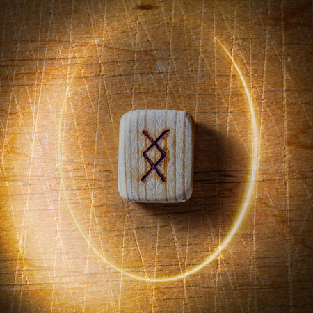 Ingwaz. Handmade scandinavian wooden runes on a wooden vintage background in a circle of light. Concept of fortune telling and prediction of the future.