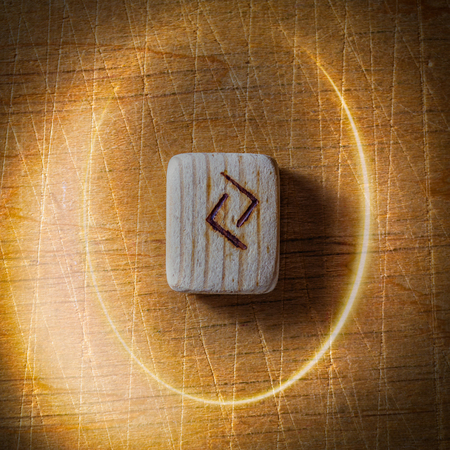 Jera. Handmade scandinavian wooden runes on a wooden vintage background in a circle of light. Concept of fortune telling and prediction of the future.