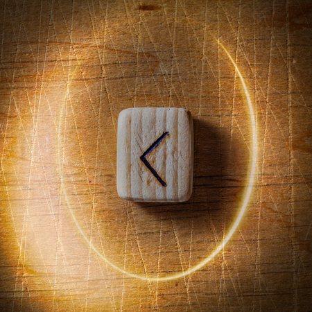 Kenaz. Handmade scandinavian wooden runes on a wooden vintage background in a circle of light. Concept of fortune telling and prediction of the future. Stock Photo