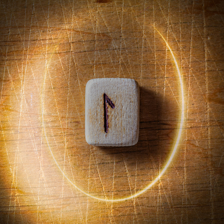 Laguz. Handmade scandinavian wooden runes on a wooden vintage background in a circle of light. Concept of fortune telling and prediction of the future.