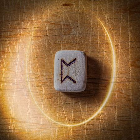 Perthro. Handmade scandinavian wooden runes on a wooden vintage background in a circle of light. Concept of fortune telling and prediction of the future.