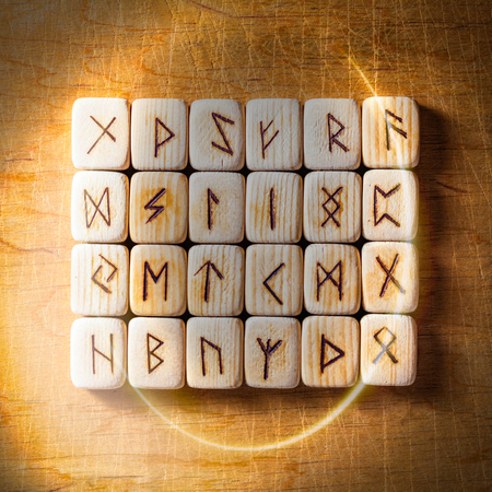 Set of Handmade scandinavian wooden runes on a wooden vintage background in a circle of light. Concept of fortune telling and prediction of the future.