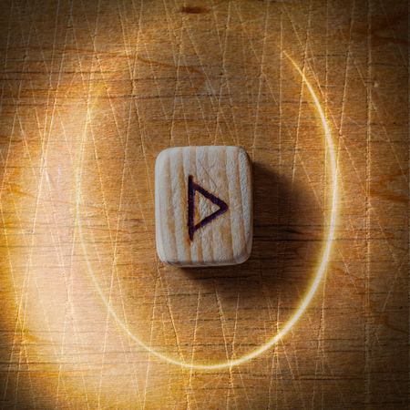 Thurisaz. Handmade scandinavian wooden runes on a wooden vintage background in a circle of light. Concept of fortune telling and prediction of the future.