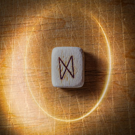 Dagaz. Handmade scandinavian wooden runes on a wooden vintage background in a circle of light. Concept of fortune telling and prediction of the future. Banco de Imagens