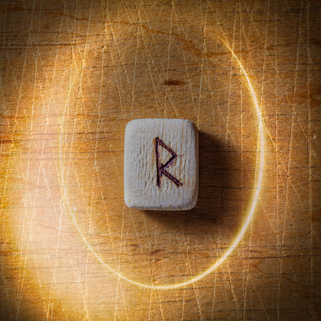 Raidho. Handmade scandinavian wooden runes on a wooden vintage background in a circle of light. Concept of fortune telling and prediction of the future.