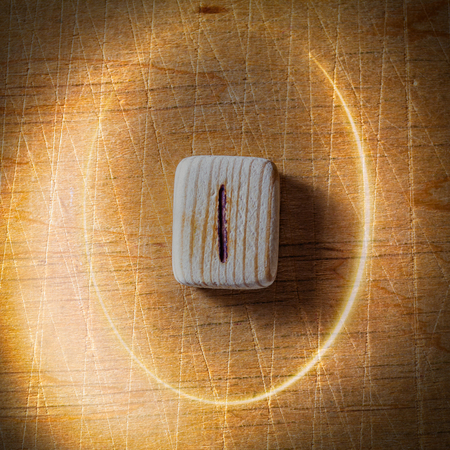 Isa. Handmade scandinavian wooden runes on a wooden vintage background in a circle of light. Concept of fortune telling and prediction of the future.