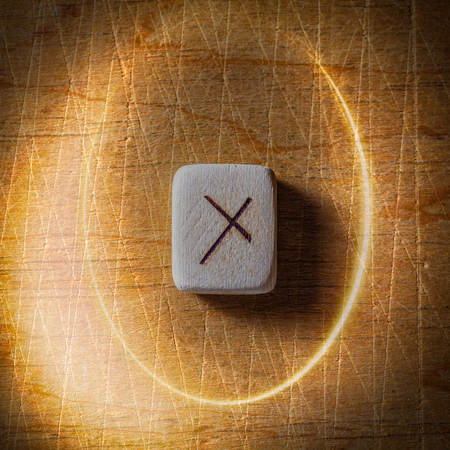 Nauthiz. Handmade scandinavian wooden runes on a wooden vintage background in a circle of light. Concept of fortune telling and prediction of the future.