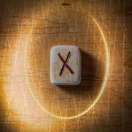 Gebo. Handmade scandinavian wooden runes on a wooden vintage background in a circle of light. Concept of fortune telling and prediction of the future.