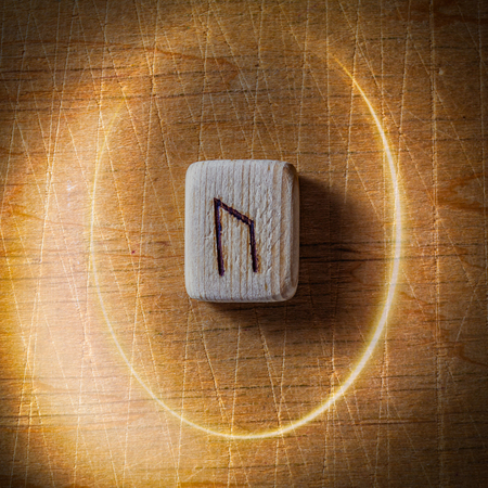 Uraz. Handmade scandinavian wooden runes on a wooden vintage background in a circle of light. Concept of fortune telling and prediction of the future. Stock Photo