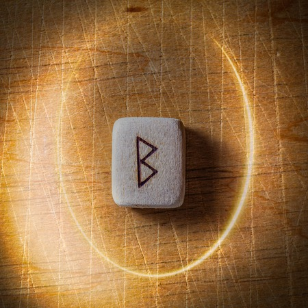 Berkano. Handmade scandinavian wooden runes on a wooden vintage background in a circle of light. Concept of fortune telling and prediction of the future.