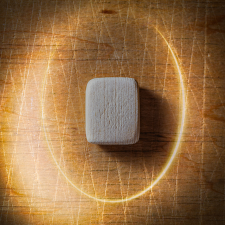 Weird, Wyrd. Handmade scandinavian wooden runes on a wooden vintage background in a circle of light. Concept of fortune telling and prediction of the future. Stock Photo