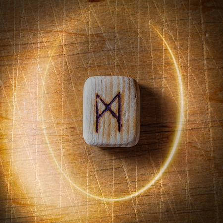 Mannaz. Handmade scandinavian wooden runes on a wooden vintage background in a circle of light. Concept of fortune telling and prediction of the future.