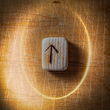 Tiwaz. Handmade scandinavian wooden runes on a wooden vintage background in a circle of light. Concept of fortune telling and prediction of the future.