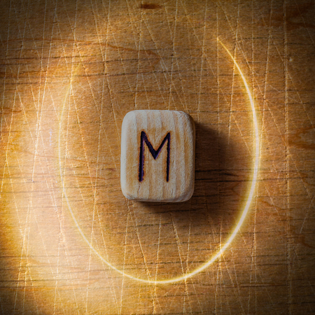 Ehwaz. Handmade scandinavian wooden runes on a wooden vintage background in a circle of light. Concept of fortune telling and prediction of the future. Stock Photo