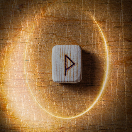 Wunjo. Handmade scandinavian wooden runes on a wooden vintage background in a circle of light. Concept of fortune telling and prediction of the future.