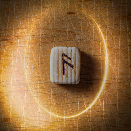 Ansuz. Handmade scandinavian wooden runes on a wooden vintage background in a circle of light. Concept of fortune telling and prediction of the future.