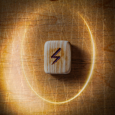 Sowilo. Handmade scandinavian wooden runes on a wooden vintage background in a circle of light. Concept of fortune telling and prediction of the future. Stock Photo