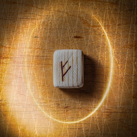 Fehu. Handmade scandinavian wooden runes on a wooden vintage background in a circle of light. Concept of fortune telling and prediction of the future.