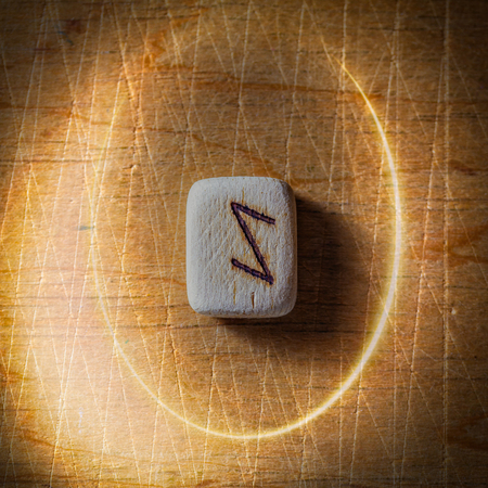 Eihwaz. Handmade scandinavian wooden runes on a wooden vintage background in a circle of light. Concept of fortune telling and prediction of the future.