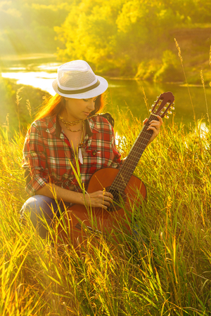 Beautiful, happy woman in the summer in the rays of the sunset with a guitar. Concept of creative freedom, fun and summer holidays. Zdjęcie Seryjne