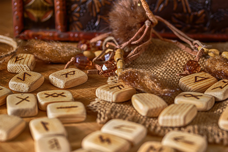 Handmade scandinavian wooden runes on a wooden vintage background. Concept of fortune telling and prediction of the future.
