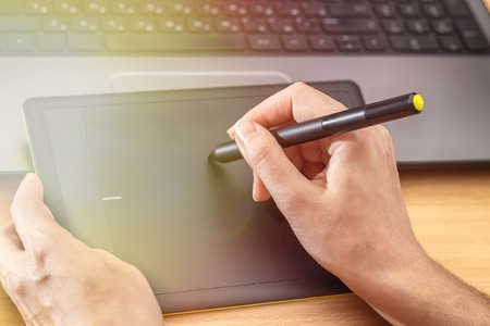 Illustrator using a graphics tablet. Womans retouchers hands using laptop and drawing tablet.