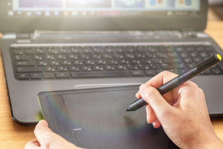 Illustrator using a graphics tablet. Woman retouchers hands using laptop and drawing tablet. 版權商用圖片