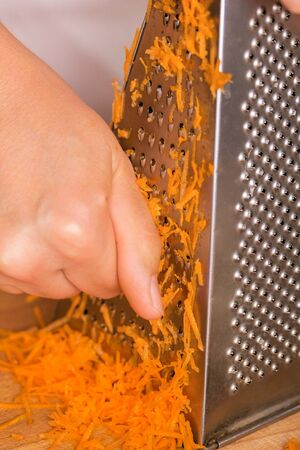 Cook rubs grated carrots close-up. Organic cooking concept.