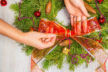 Florist makes a Christmas wreath of fir branches. Top view of female hands. Flat lay. Ribbon decoration.
