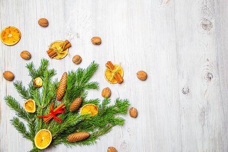 Composizione di Natale e Capodanno. Rami di pino, bastoncini di cannella, fettine essiccate di arancia e noci. Concetto di Natale e Capodanno. Disposizione piatta.